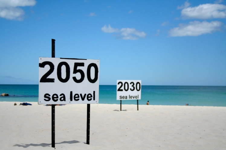 Signs posted at a beach in Australia show where sea levels are predicted to be in coming decades. (Credit:  go_greener_oz/Flickr Creative Commons)